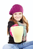 Teenager in winter clothes holding cup of tea Stock Images