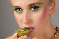 Teenager With Kiwi And Matching Makeup Royalty Free Stock Photos