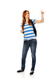 Teenager woman with backpack pointing for soomething Royalty Free Stock Photo