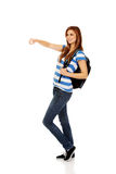Teenager woman with backpack pointing for soomething Royalty Free Stock Image