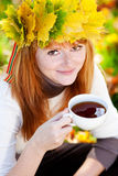 Teenager woman in a wreath of maple leaves with cu Royalty Free Stock Photos
