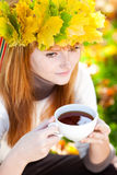 Teenager woman in a wreath of maple leaves with cu Stock Images