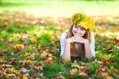 Teenager woman in a wreath of maple leaves lying o Royalty Free Stock Images