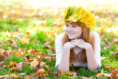 Teenager woman in a wreath of maple leaves lying o Royalty Free Stock Photography