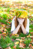 Teenager woman in a wreath of maple leaves lying o Royalty Free Stock Photos