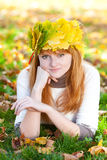 Teenager woman in a wreath of maple leaves lying o Stock Photo