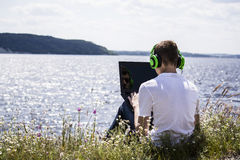 Teenager working for a laptop. On the bank of the river in summer Stock Images