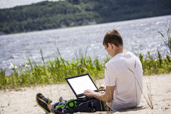 Teenager working for a laptop on the beach. In summer Royalty Free Stock Image