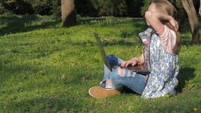 Teenager working on laptop in nature. The girl is sitting on the grass in the park. On a sunny day in the fresh air with a laptop. stock video