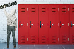 Teenager writing boring. Back view of cool teenager writing word 'boring' with graffiti spray can in school corridor with red lockers. 3D Rendering Royalty Free Stock Image