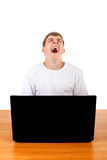 Teenager yawning behind Laptop. Tired Teenager Yawning at the Desk with Laptop Isolated on the White Background Stock Images