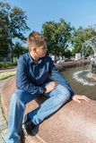 Teenager of 14 years is sitting near fountain stock photography