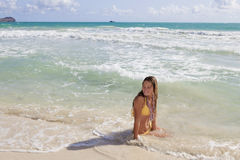 Teenager in a yellow bikini in the ocean Stock Image