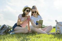 Teenagermädchen im Hut und in der Sonnenbrille auf dem grünen Rasen im Erholungspark ihre Cocktails, goldene Stunde genießend stockfotografie