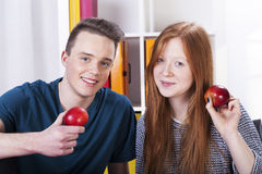 Teenagers with apples. Happy male and female teenagers are holding apples Royalty Free Stock Photos