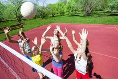 Teenagers with arms up are playing volleyball Stock Photos