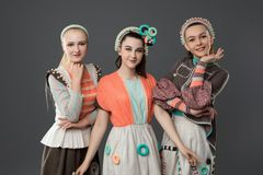 Teenagers in artistic fashion dresses view. Pretty teenagers in artistic fashion dresses view against gray wall royalty free stock photo