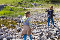 Teenagers with backpacks cautiously cross the creek along the rocks, hiking into the forest. Summer vacation. stock photos
