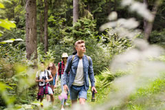 Teenagers with backpacks hiking in forest. Summer vacation. Teenagers with backpacks hiking in forest. Summer vacation adventure Stock Images