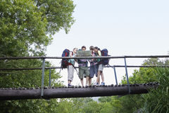 Teenagers With Backpacks Reading Map On Bridge Royalty Free Stock Photography