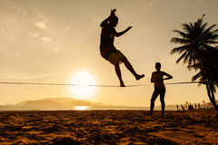 Teenagers balance on slackline silhouette Stock Photography