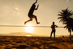 Teenagers balance on slackline silhouette Royalty Free Stock Photos
