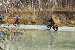 Children ride bicycles on the ice of the river in the spring. stock images
