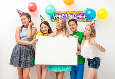 Teenagers at a birthday party holding banner. Group of teenagers at a birthday party holding white banner Stock Photos