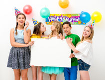 Teenagers at a birthday party holding banner. Group of teenagers at a birthday party holding white banner Royalty Free Stock Photos