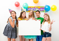 Teenagers at a birthday party holding banner. Group of teenagers at a birthday party holding white banner Stock Images