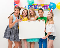 Teenagers at a birthday party holding banner. Group of teenagers at a birthday party holding white banner Stock Photo