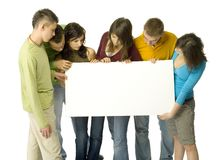 Teenagers with board. Group of 6 teenagers holding white blank board. They're looking at it. White background behind them Royalty Free Stock Image