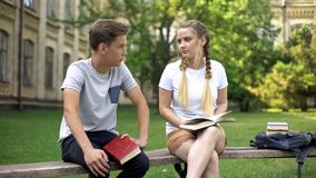 Teenagers bored with studies having conversation, exhausted from reading books stock photo