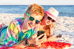 Teenagers (boy and girl) using smart phone and listening music. royalty free stock photography