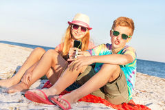 Teenagers (boy and girl) using smart phone and listening music.  Stock Photos