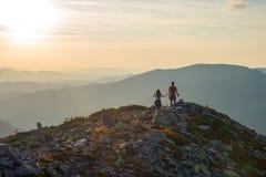 Teenagers boy and a girl walk along a stony mountain range Royalty Free Stock Photography