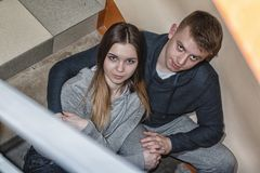 Teenagers boyfriend and girlfriend sit on the steps in block of flats. Homeless teenagers boyfriend and girlfriend sit on the steps in block of flats royalty free stock image