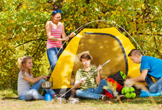 Teenagers build yellow tent themselves in forest. Teenagers build yellow tent themselves in the forest at the camping site together Stock Image
