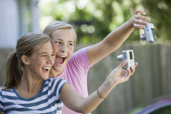Teenagers with cameras. Teen girls taking each others picture with digital cameras Royalty Free Stock Images