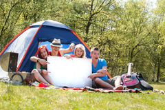 Teenagers on a camping with an empty sign board Stock Images