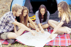 Teenagers camping look at a map. Near a tent Stock Photos