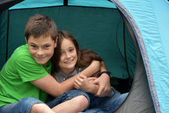Teenagers at camping vacations. Siblings at the campsite, who relax in a tent and fool around Stock Image