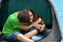 Teenagers at camping vacations. Siblings at the campsite, who relax in a tent and fool around Stock Photo