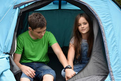 Teenagers at camping vacations. Siblings  at camping relaxing in a tent Royalty Free Stock Photography