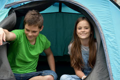 Teenagers at camping vacations. Siblings  at camping relaxing in a tent Royalty Free Stock Images