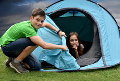 Teenagers at camping vacations. Siblings in tent  at camping enjoying nature Royalty Free Stock Image