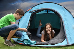 Teenagers at camping vacations. Siblings in tent  at camping enjoying nature Royalty Free Stock Images