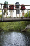 Teenagers Carrying Backpacks On Bridge Looking Down Royalty Free Stock Image