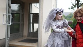 Teenagers celebrate Halloween in costumes and with make-up. Children scream Trick or Treat and get candy in their. Teenagers celebrate Halloween in costumes and stock footage