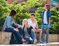 Teenagers chatting outdoors in town Royalty Free Stock Image
